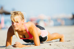 Sportswoman in abs plank on beach Royalty Free Stock Photo