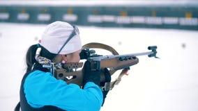 Sportswoman is aiming in process of biathlon training. 4K stock video footage