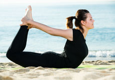 Sportswoman in black T-shirt is practicing set of stretching exe Royalty Free Stock Photography
