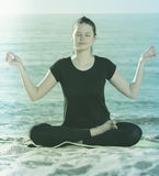 Sportswoman in black T-shirt is sitting and practicing yoga Stock Photos