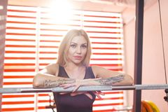 Sportswoman, blond, stands in the gym leaning hands against the metal bar of the barbell. A beautiful European woman sportswoman, blond with long hair, stands Stock Photography