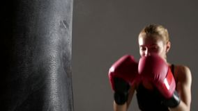 Sportswoman boxer knocks out of the punching bag. Slow motion. Sportswoman boxer knocks out of the punching bag of flies talc, dressed in black top visible to stock video
