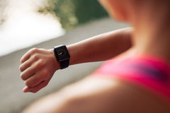 Sportswoman checking time on smartwatch Royalty Free Stock Image
