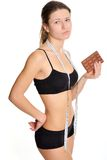Sportswoman with chocolate. The problem and the temptation while. The girl wants chocolate. Harmful, sweet and tasty food. Sports and chocolate do not mix. If Stock Photos