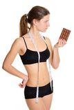 Sportswoman with chocolate. The problem and the temptation while Royalty Free Stock Image