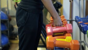 Sportswoman choose dumbbells to train in sport gym. Fit woman in black pants, t-shirt choosing equipment for working out. Colorful orange, pink, yellow sporty stock video