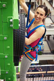Sportswoman is climbing on the wall in indoor sport center Royalty Free Stock Photos