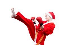 Sportswoman in clothes as Santa Claus beats high kick forward Stock Photos