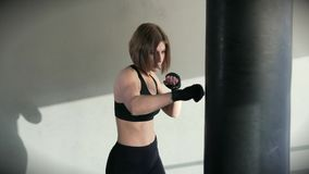 The sportswoman confidently strikes her hands in the boxing bag in the gym. A woman in a sport suit works out a boxing blow on a sports equipment. The athlete stock video