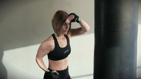 The sportswoman confidently strikes her hands in the boxing bag in the gym. A woman in a sport suit works out a boxing blow on a sports equipment. The athlete stock video footage