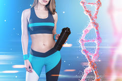 Sportswoman and dna chain. Close up of a sportswoman wearing a blue, black and white sportswear and standing against blue background with a dna chain to her royalty free stock photography