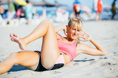 Sportswoman doing abs exercise on beach. Portrait of active smiling sportswoman doing abs exercise on sand in sunlight Royalty Free Stock Photo