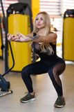 A sportswoman doing an exercise of deep squats, balancing herself with hands, in the gym. A beautiful sportswoman is a European woman, dressed in a black tight Royalty Free Stock Image