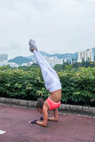 Sportswoman doing handstand yoga exercise standing on her forearms with straight legs  path in the park  view of city Royalty Free Stock Photo
