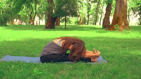 Sportswoman doing paschimottanasana outdoors. Side view slim woman sitting on blue yoga matt trains in park. caucasian girl with long curly hair trains at the stock video