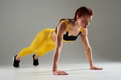 Sportswoman doing plank excercise. In studio Stock Photography