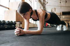 Sportswoman doing plank exercise in gym. Serious young sportswoman doing plank exercise in gym royalty free stock photos