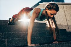 Sportswoman doing push ups on steps. Strong young woman doing push ups on steps outdoors. Sportswoman doing push ups exercises in morning Stock Photography