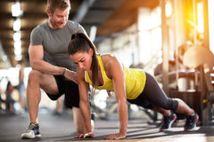 Sportswoman doing pushups with assisting stock photography