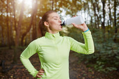 Sportswoman drinking isotonic drink. Portrait of young sportswoman drinking isotonic drink Royalty Free Stock Images