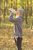 Sportswoman drinking water during jogging royalty free stock images