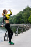 Sportswoman drinking water after running Stock Photography