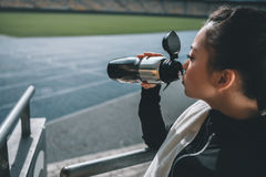 Sportswoman drinking water and towel on running track on stadium Royalty Free Stock Photos