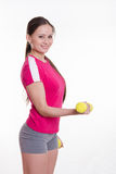 Sportswoman with dumbbells workout performs Royalty Free Stock Photos