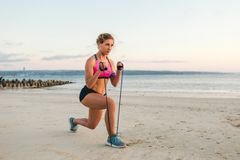 Sportswoman in earphones with smartphone in armband case doing exercise with stretching band. On beach stock images