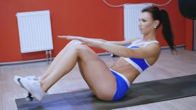 Sportswoman on exercise mat doing situps and doing abs with weights 4K.  stock video