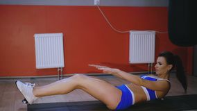 Sportswoman on exercise mat doing situps and doing abs with weights 4K.  stock video footage
