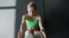 Sportswoman on exercise mat doing abs workout in gym. Muscular female athlete doing abs workout. Sportswoman on exercise mat doing situps in gym. Muscular stock video footage