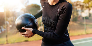 Sportswoman exercising with fitness ball on tennis court Royalty Free Stock Image