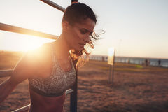 Sportswoman exercising on outdoor workout equipments Stock Images