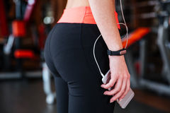 Sportswoman with fitness tracker holding cell phone in gym royalty free stock images