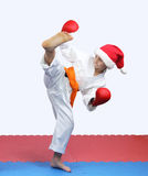 Sportswoman in hat Santa Claus is doing circular kick leg Stock Images