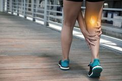 Hamstring pain. Sportswoman having pain in her hamstring, vew from the back Stock Photo