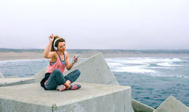 Sportswoman with headphones sitting and dancing. Young sportswoman with headphones sitting and dancing Stock Image