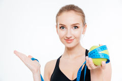 Sportswoman holding apple with measuring tape and  copyspace on palm Stock Images