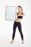 Sportswoman holding blank board and pointing on it Stock Images