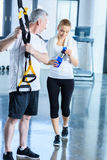 Sportswoman holding sport bottle and senior sportsman with resistance band talking Stock Photos