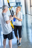 Sportswoman holding sport bottle and senior sportsman with resistance band talking Royalty Free Stock Photo