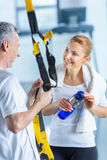 Sportswoman holding sport bottle and senior sportsman with resistance band talking Stock Photo