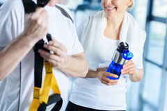 Sportswoman holding sport bottle and sportsman with resistance band talking. In sports center Royalty Free Stock Images