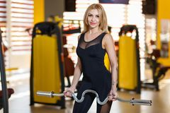 Sportswoman holds a heavy w-bar in arms, in the gym. An attractive European sportswoman, a blonde with long hair, is dressed in a black tight-fitting sports Stock Photography