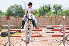The sportswoman on a horse has successfully completed the jump across the barrier Royalty Free Stock Photo