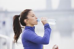 Sportswoman hydrating, fitness and wellness. Women running by the water Royalty Free Stock Images
