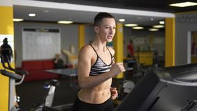 A sportswoman is intensively running on a treadmill, using hands in fitness club stock footage