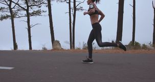 Sportswoman jogging on countryside road in morning stock footage