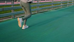 Woman is running in stadium on open road, close-up of legs. Sportswoman is jogging in running track in stadium, view on legs. She is training and keeping fit stock video footage
